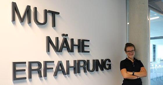 """Frau steht vor weißer Wand mit den Wörtern """"Mut"""", """"Nähe"""", """"Erfahrung"""""""